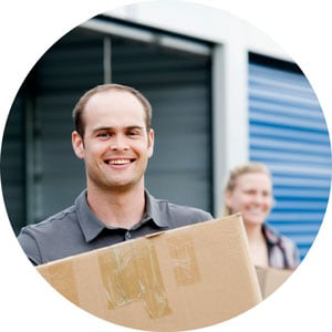 Photo of a smiling man carrying a moving box